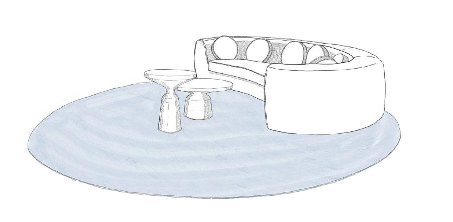Runde Couch und Beistelltische platziert auf einem runden Teppich