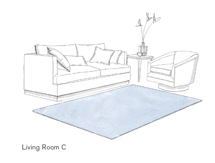Bläulicher Teppich platziert vor Couch und Fauteuil mit Beistelltisch