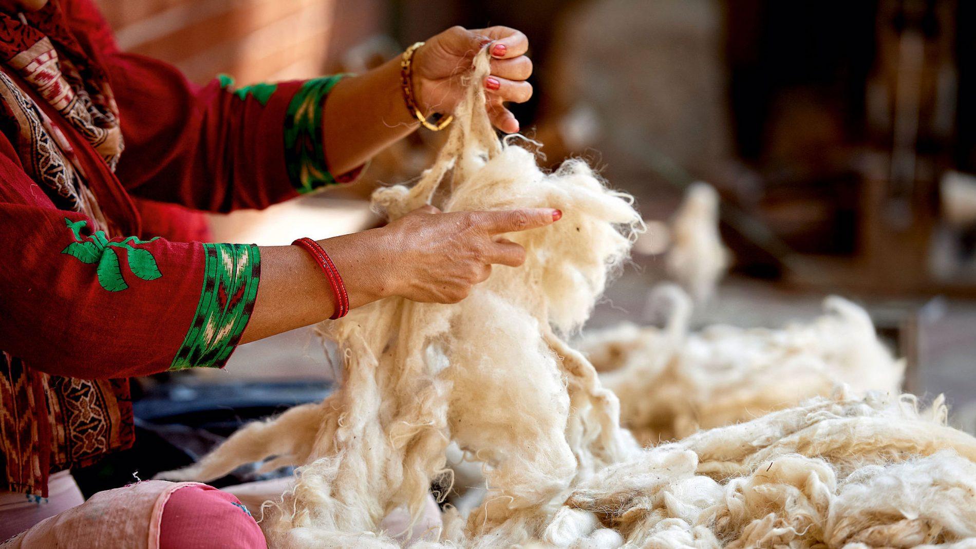 Knüpferin in rotem Kleid bereitet eine große Menge an Wolle für die Produktion vor