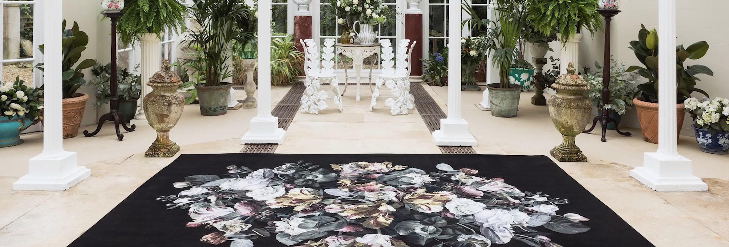Großer Raum mit vier weißen Säulen, ein schwarzer Teppich mit malerischen Blumenmuster liegt mittendrin, umringt von zahlreichen Topfpflanzen