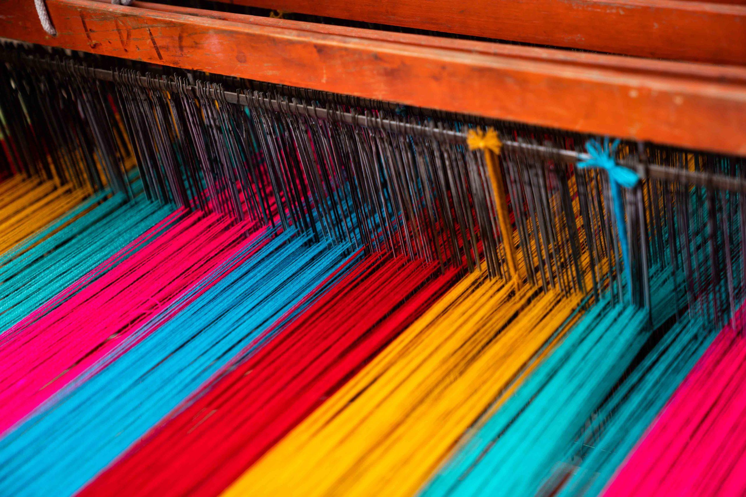 Nahaufnahme eines horizontalen Webstuhls mit dichten Fäden in rot, blau und gelb